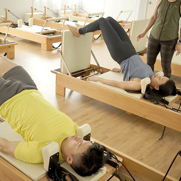 Two Students prepare to jump on the reformer during the Reformer Jump Pilates class.