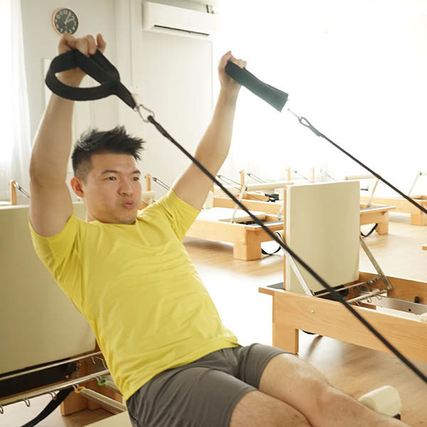 A Student doing overhead hands in straps during the Super Power Pilates class.